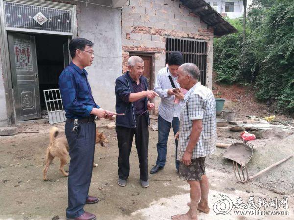 工会主席管长元(左一)正在慰问贫困村民
