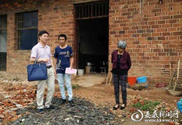 罗建国书记(左一)与村民交流,详细了解其家庭情况