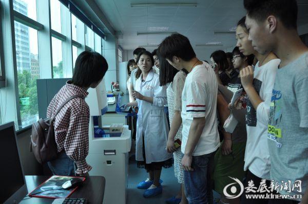 图为检验科工作人员正在给学生讲解血液检验器械