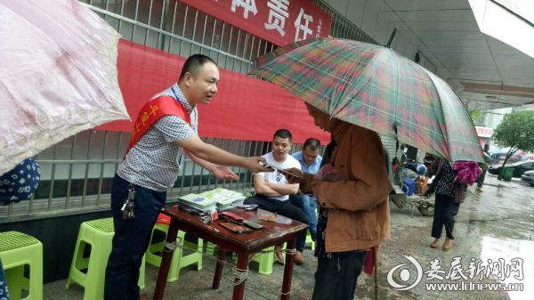 刘欣给过往群众发放宣传手册