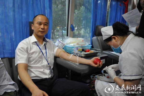 图为太平人寿保险娄底中心支公司总经理徐伟正在献血