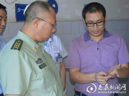 消防支队政委刘雪峰向主治医生询问受伤战士伤情