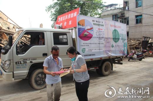 宣传车和宣传员在观化社区开展灾后防病宣传
