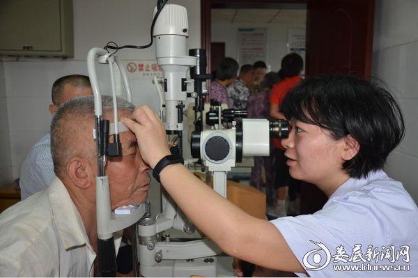 娄底爱尔眼科医院廖圣医生正在为白内障术后患者检查恢复情况
