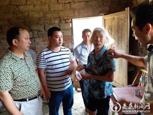 图为易姣文受邵子军委托将一万元现金交到李买英手中