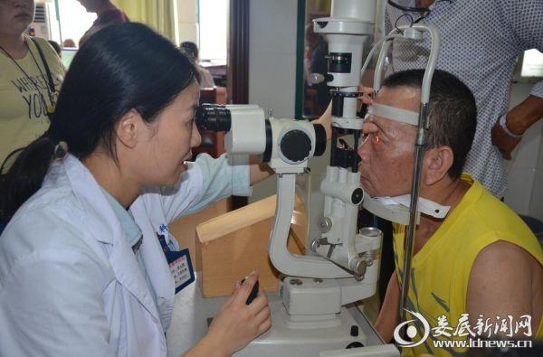 娄底爱尔眼科医院聂元辉主任正在为彭真良老人做术后检查