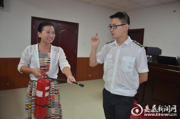 消防安全指导老师教现场学员如何使用干粉灭火器
