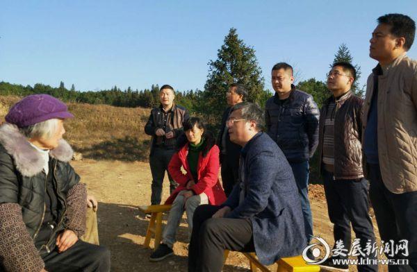 图为梁小兵在跑马村易地搬迁户徐凤响家了解情况,与群众促膝而谈