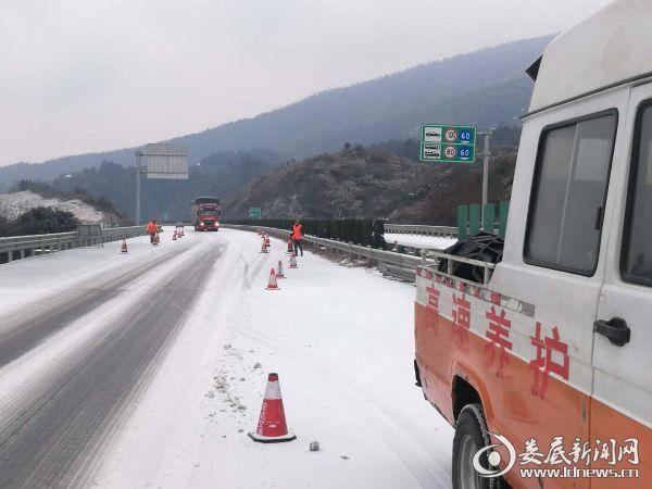 养护工对新溆高速娄底段积雪结冰桥梁路段维护锥桶、标志标牌,压缩至一条车道减速通行。