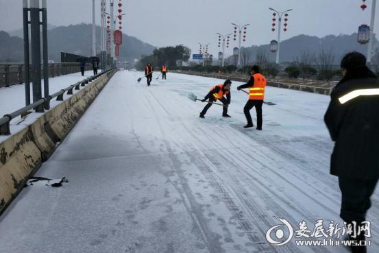 (1月26日清晨,冷水江市政在新城大桥铺撒融雪剂)