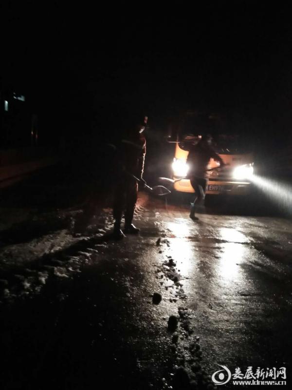 (1月26日晚,冷水江市公路人在S217三尖镇石槽路段铺撒融雪剂)