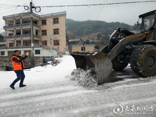 (1月26日,冷水江市公路局出动铲车在S312除冰)