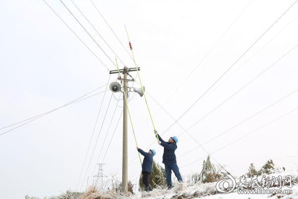 图为国网娄底供电公司城北供电所电力工人肖利、吴运松挥舞除冰棒,在为线路除冰。(肖璋 摄)
