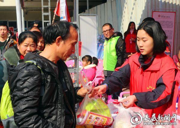 """志愿者为返乡市民送上""""爱心包""""和《便民手册》"""