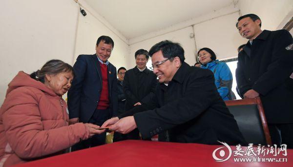 王少峰与五保户廖加南老人促膝交谈,并送上慰问金