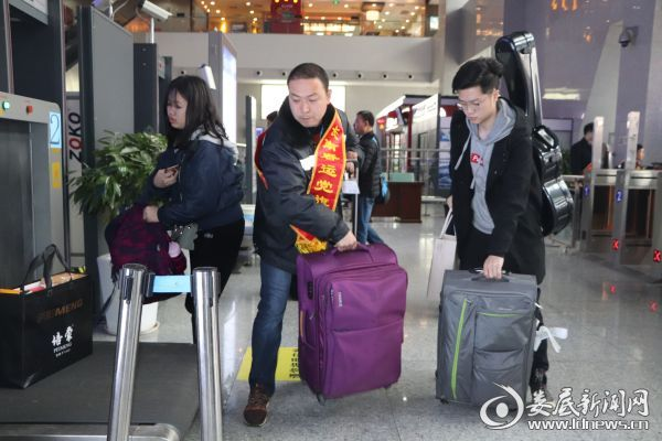(志愿服务人员帮旅客把行李提上安检机)