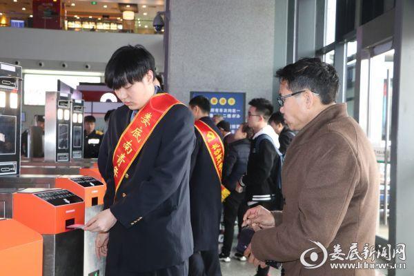 (志愿服务人员给不熟悉人脸识别验票的旅客示范操作)