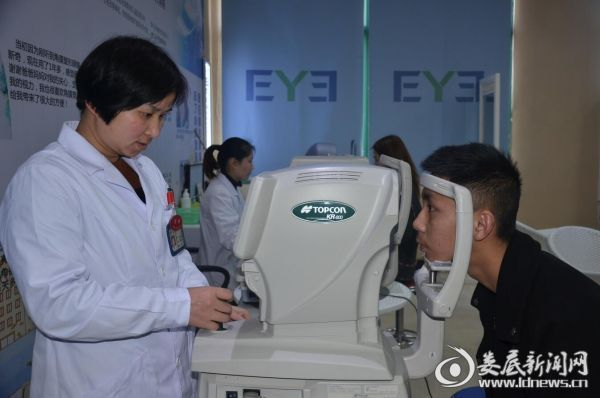 娄底爱尔眼科医院屈光中心的医务人员正在为李禹铖做术后检查