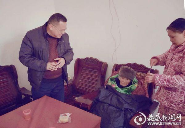 (涟源市民政局相关负责人仔细询问老人的日常起居和身体情况)