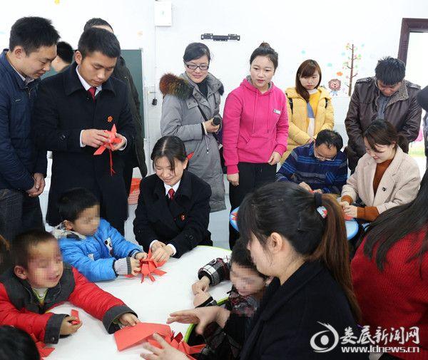 新化法院的干警和孩子们一起折红花