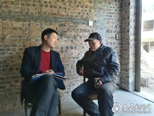 (图为县安监局副书记副局长王坚志和贫困对象罗成忠在促膝交谈)