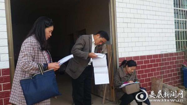 枫坪镇主要领导干部在贫困户家仔细核对帮扶手册信息
