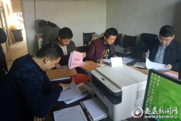 枫坪镇主要领导和帮扶干部在仔细浏览相关工作台账