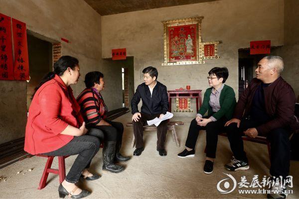 几条板凳围坐而谈,李荐国详细询问颜仁果家里有几口人、因什么致贫、收入来源是什么