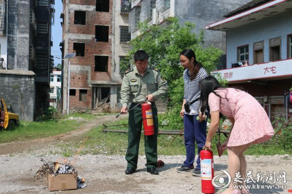 (大队宣传员现场示范了如何使用干粉灭火器扑灭油盆大火,并手把手指导全园教师进行了操作实践)