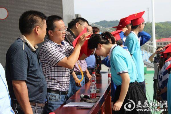 校领导为学生代表佩戴成人帽