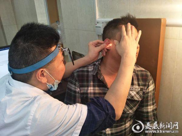 51病室主任李泉为患者检查耳部