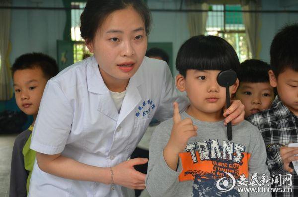 娄底爱尔眼科医院的医务人员细心为检测视力的孩子遮挡眼睛