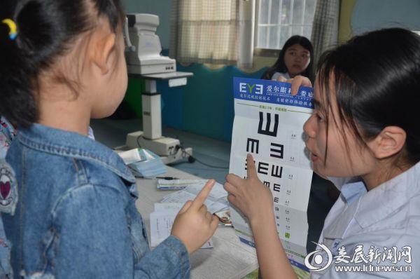 娄底爱尔眼科医院义务人员耐心指导孩子们正确识别视力表