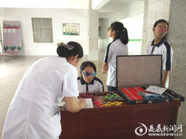 (娄底爱尔眼科医院医务人员对符合救助要求的学生一对一进行验光配镜服务)