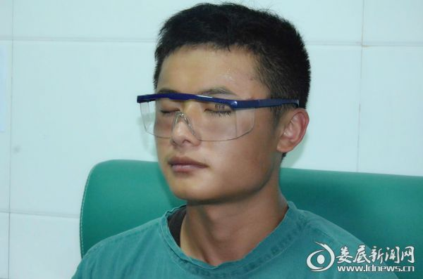 (娄底爱尔眼科医院医务人员为周贤辉戴上防护眼镜)
