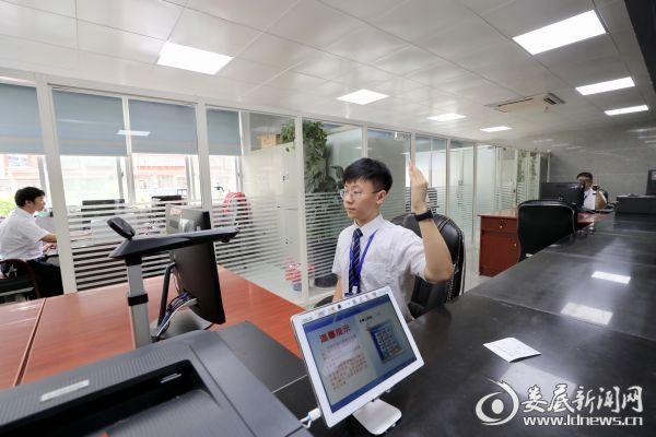 市政务服务中心窗口工作人员向下一个办理业务的市民举手示意