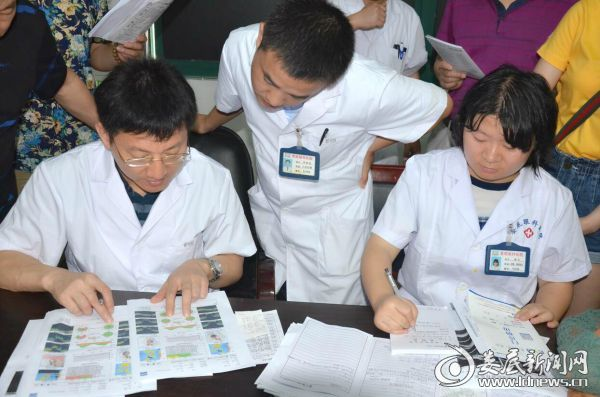 段宣初教授(左一)和娄底爱尔眼科医院住院部主任苏继勇(左二)交流患者病情