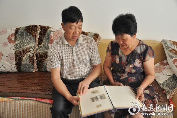 父母在家中翻阅儿时的照片