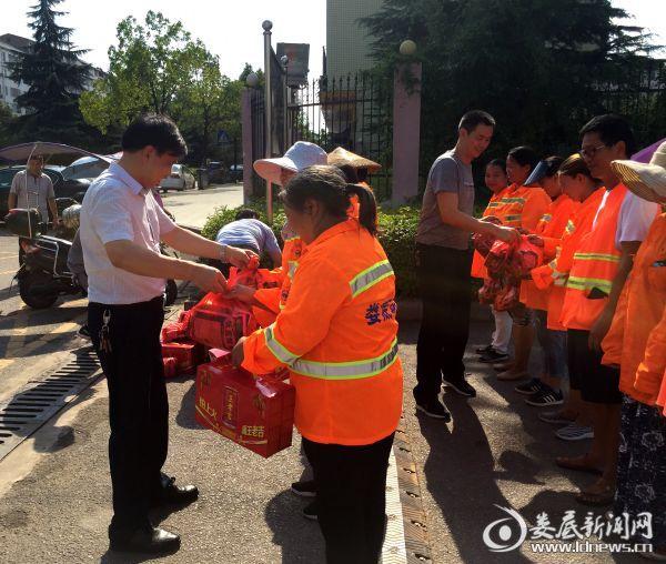 市城管执法局党委书记、局长谢万春给环卫工人送去防暑药品和凉茶