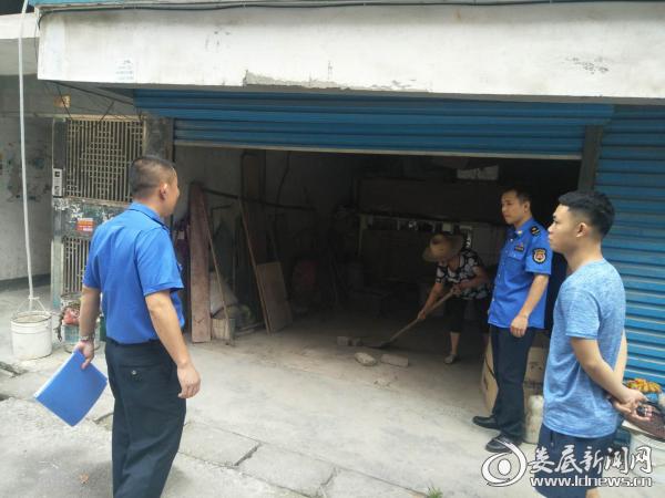 (8月8日,城管执法人员复查整改结果,当事人正在清扫车库)