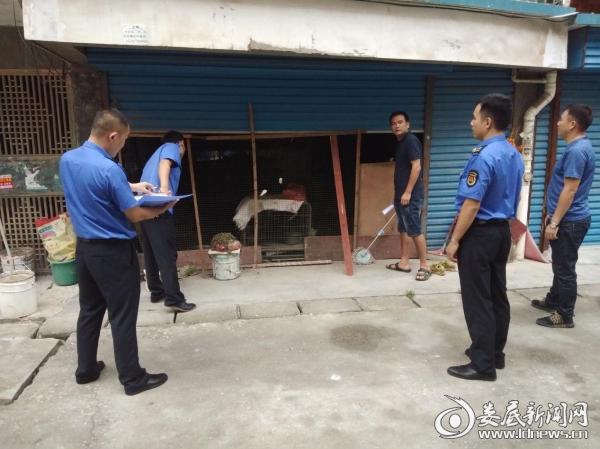 (8月7日,城管执法人员现场查看车库内养鸡情况)