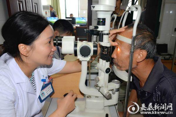 娄底爱尔眼科医院眼底病中心主任唐玖鸿为贺安帮老人做术后复查