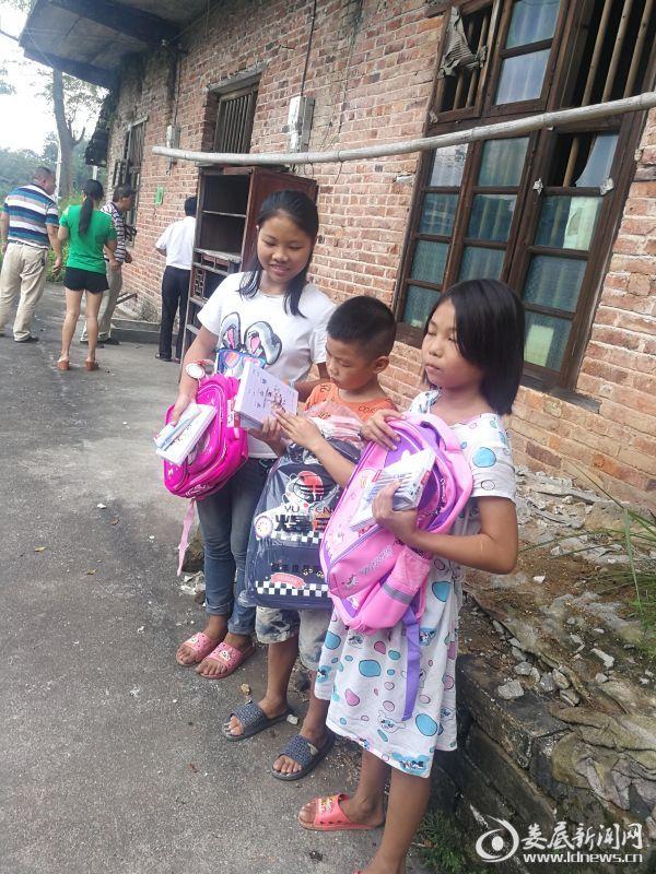 抱着崭新的学习用品,他们幸福的笑了