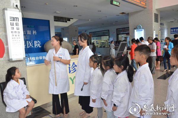 娄底爱尔眼科医院的医务人员教孩子们如何进行视力检测