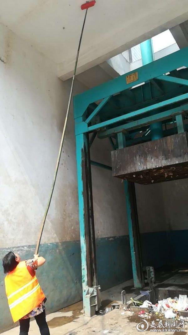 环卫工人清理垃圾站蜘蛛网