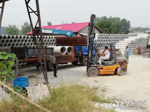 工作人员正在转运水源地保护区内涵管厂设备及产品