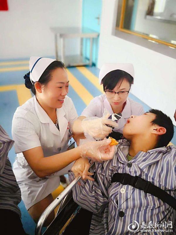医务人员喂月饼给病友吃