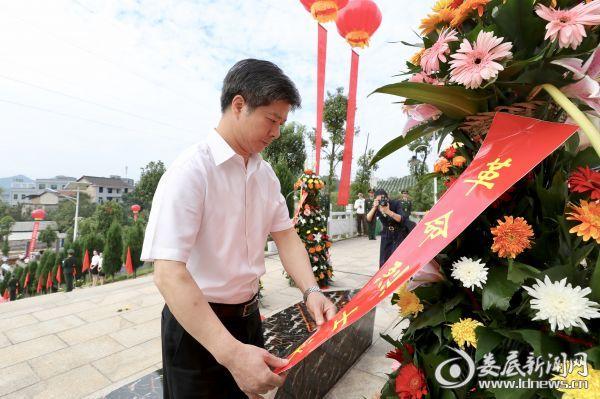 烈士纪念碑前,李荐国神情庄重,仔细整理花篮上的红色缎带