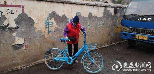 志愿者刘美英扶好倒地的共享单车