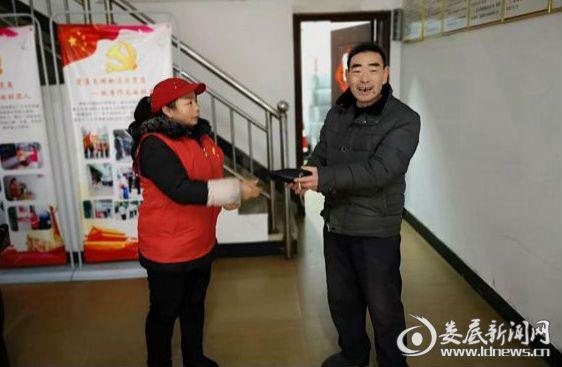 志愿者谭解元把捡到的钱包交还刘先生